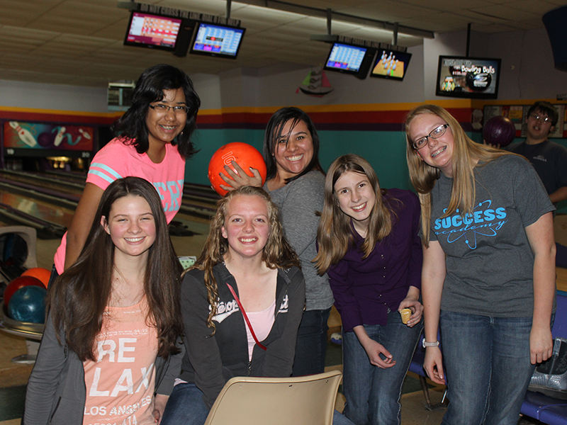 students at a bowling alley smilimg for the camera, holding a bowling ball